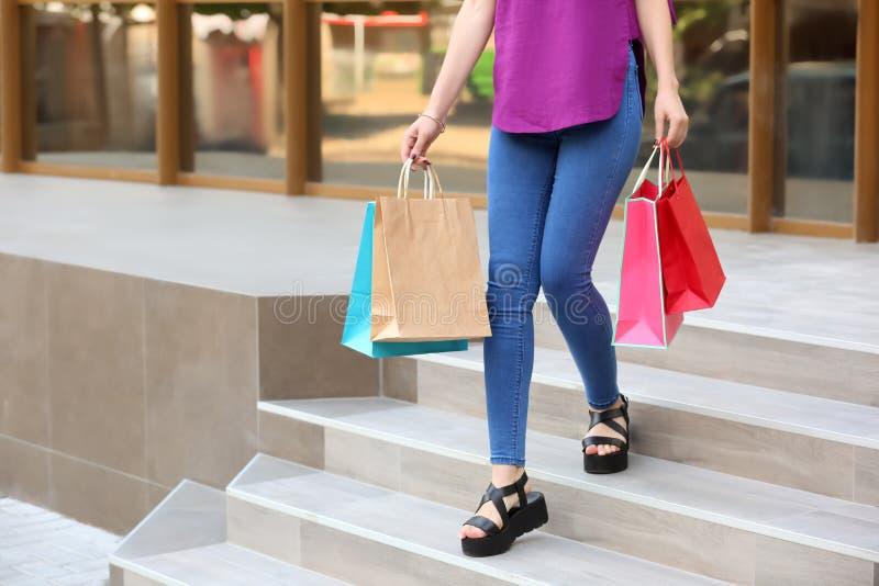 Härlig ung kvinna med shoppingpåsar på trappa nära lager utomhus arkivfoto