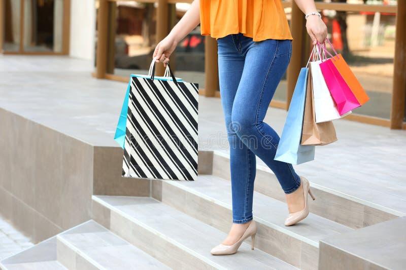 Härlig ung kvinna med shoppingpåsar på trappa nära lager utomhus arkivbild
