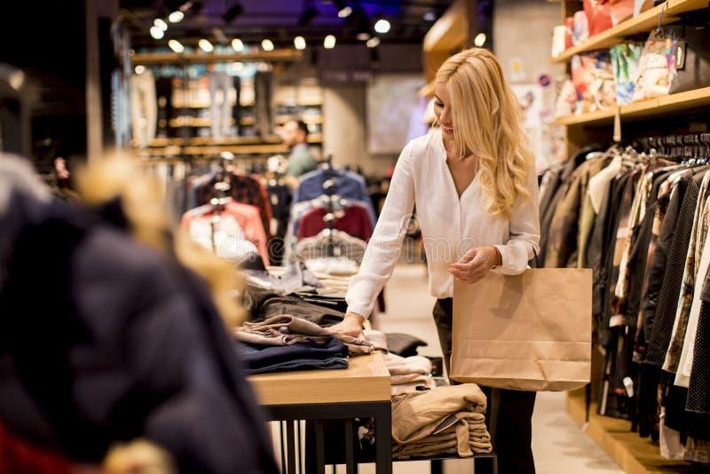 Härlig ung kvinna med shoppingpåsar som står på klädlagret arkivbilder