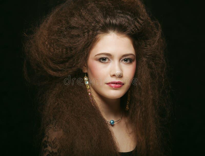 Härlig ung kvinna med smink för lockigt hår och afton Smycken och skönhetbegrepp studio för konstmodefoto royaltyfri fotografi