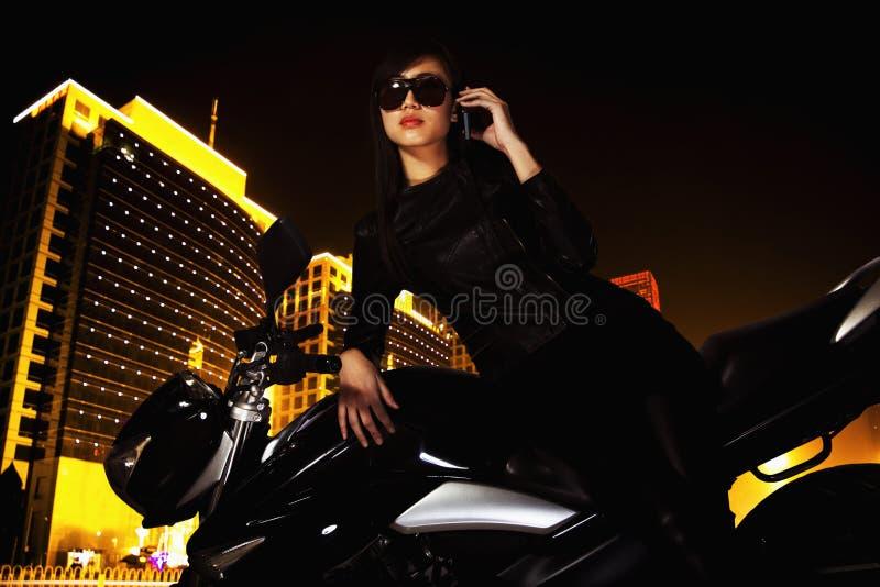Härlig ung kvinna med solglasögon som talar på telefonen och benägenheten på hennes motorcykel på natten fotografering för bildbyråer