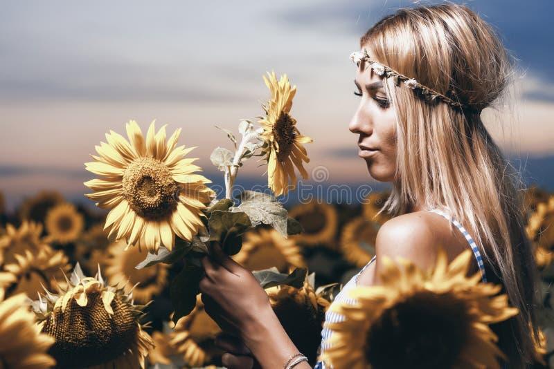 Härlig ung kvinna med solrosen som poserar i solrosorna fi royaltyfri fotografi