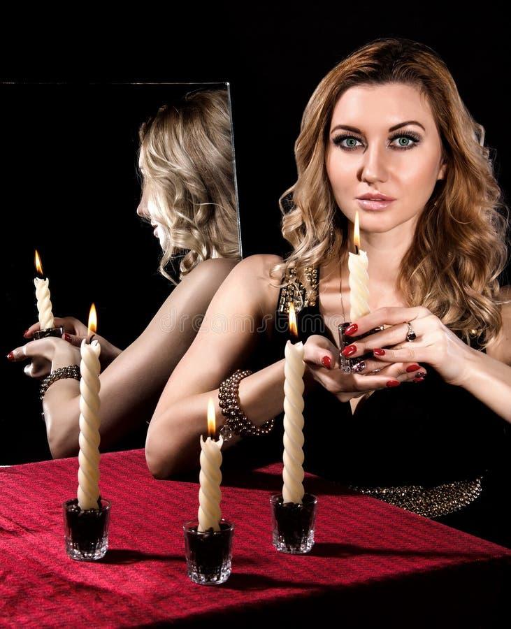 Härlig ung kvinna med stearinljus nära spegeln royaltyfria bilder