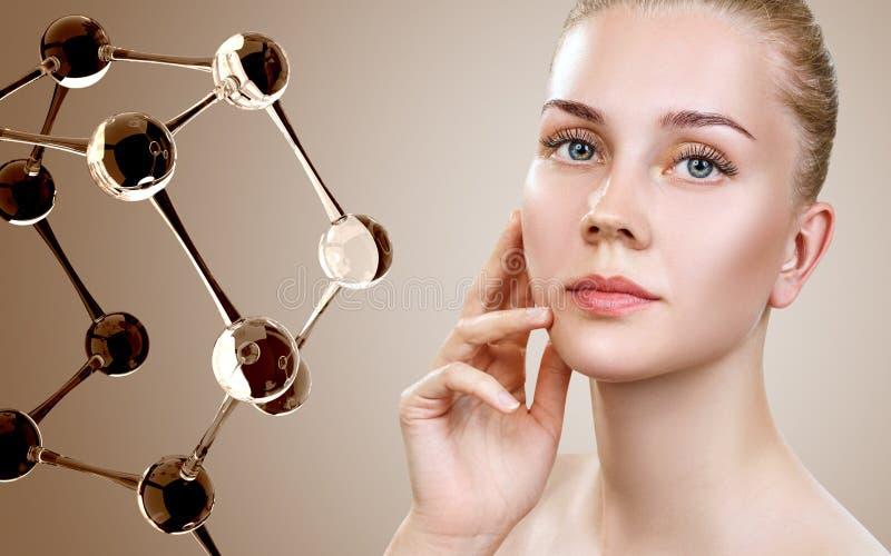 Härlig ung kvinna nära beigea exponeringsglasmolekylar arkivbild