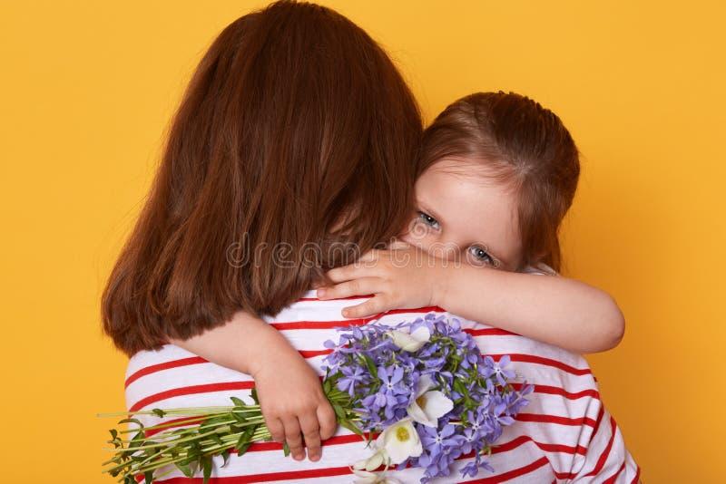 Härlig ung kvinna och hennes charmig liten dotter som inomhus kramar Barnet gratulerar mamman med mors dag, ger blommor, royaltyfria bilder