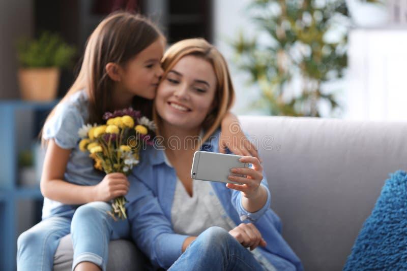 Härlig ung kvinna och hennes dotter som tar selfie, medan sitta på soffan hemma royaltyfria foton