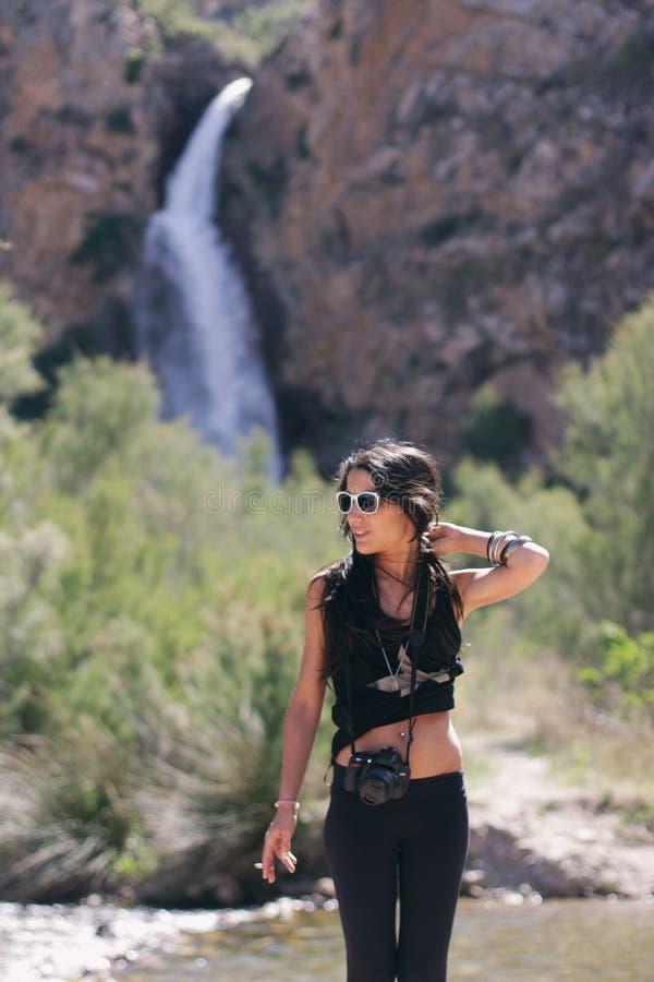 Härlig ung kvinna på berget och en vattenfall arkivbilder