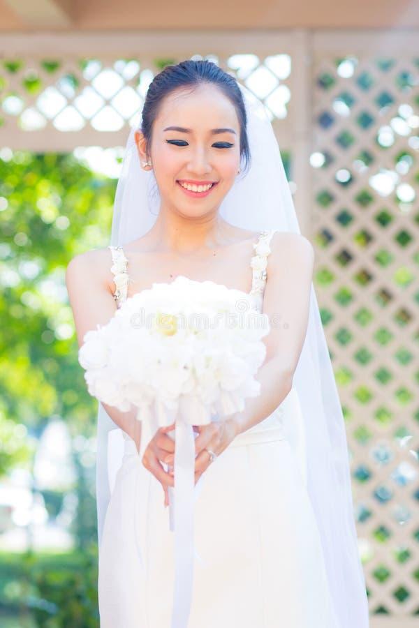 härlig ung kvinna på bröllopdag i den vita klänningen i trädgården arkivbilder