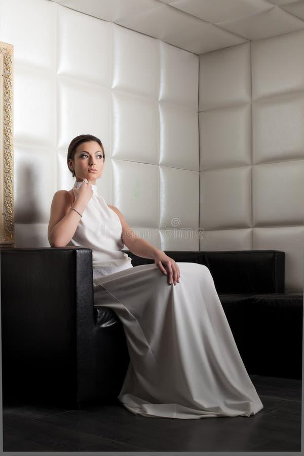 Härlig ung kvinna på den enorma vitsofaen royaltyfria foton