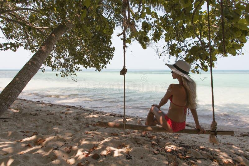 Härlig ung kvinna på en gunga som vilar på den exotiska stranden wellness livsstil arkivfoto