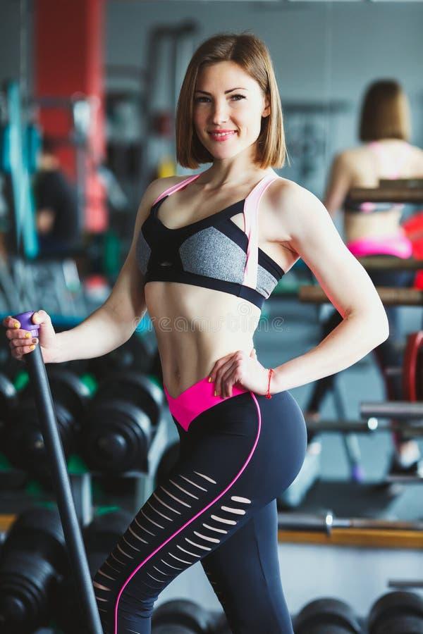 Härlig ung kvinna på idrottshallen royaltyfri foto