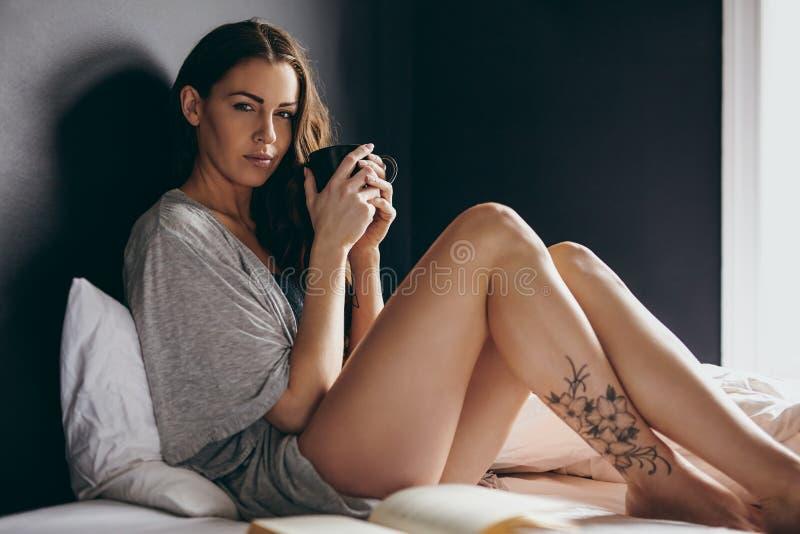 Härlig ung kvinna på säng med en kopp kaffe royaltyfri foto