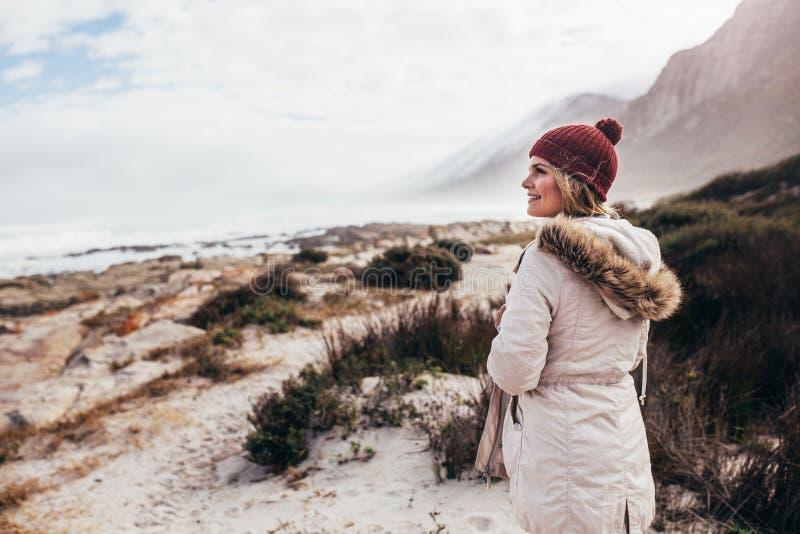 Härlig ung kvinna på stranden på vinterdag arkivbilder