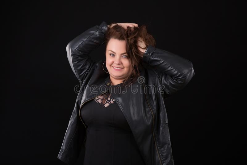 Härlig ung kvinna plus format med den stora bysten i bakgrund för svart för underkläder- och läderomslag n arkivbild