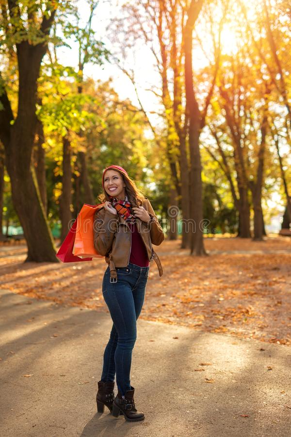 Härlig ung kvinna som är lycklig, når att ha shoppat och att ha gått i en parkera royaltyfri bild