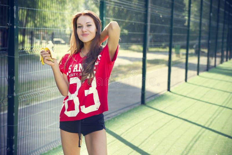 Härlig ung kvinna som äter en banan royaltyfria foton