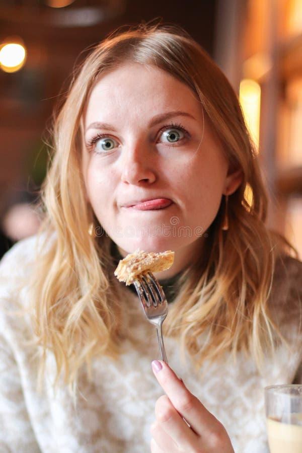 Härlig ung kvinna som äter hemlagade pannkakor i coffee shop, matblogger arkivfoto