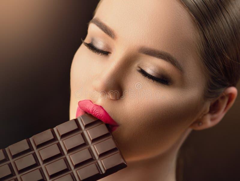 Härlig ung kvinna som äter mörk choklad Skönhetmodellflicka som tycker om choklad arkivfoto