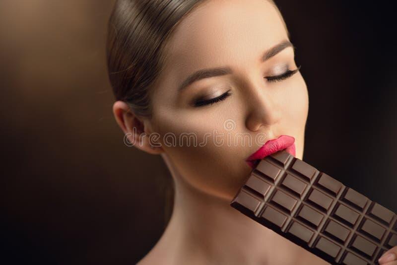 Härlig ung kvinna som äter mörk choklad Skönhetmodellflicka som tycker om choklad arkivbild