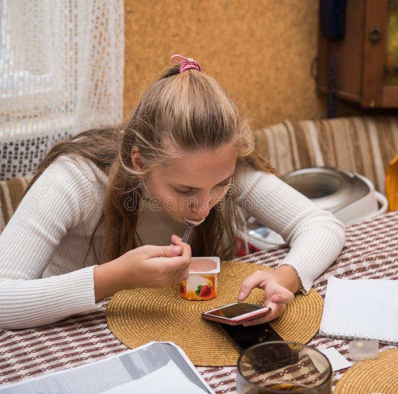 Härlig ung kvinna som överför meddelandet med hennes smartphone, medan äta yoghurt royaltyfria bilder