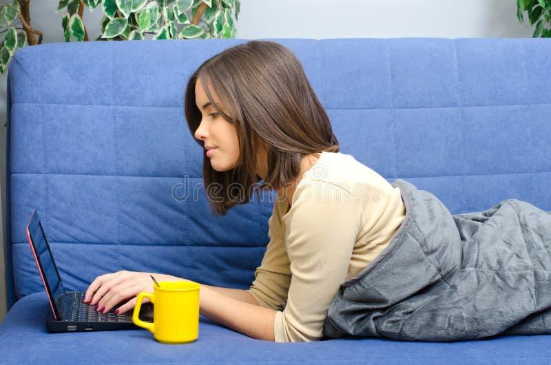 Härlig ung kvinna som använder anteckningsboken som ligger på soffan som dricker kaffe arkivfoton