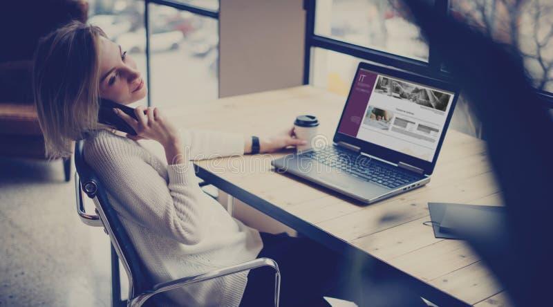 Härlig ung kvinna som använder bärbara datorn och smartphonen på trätabellen i coworking studio Begrepp av folk som arbetar med fotografering för bildbyråer