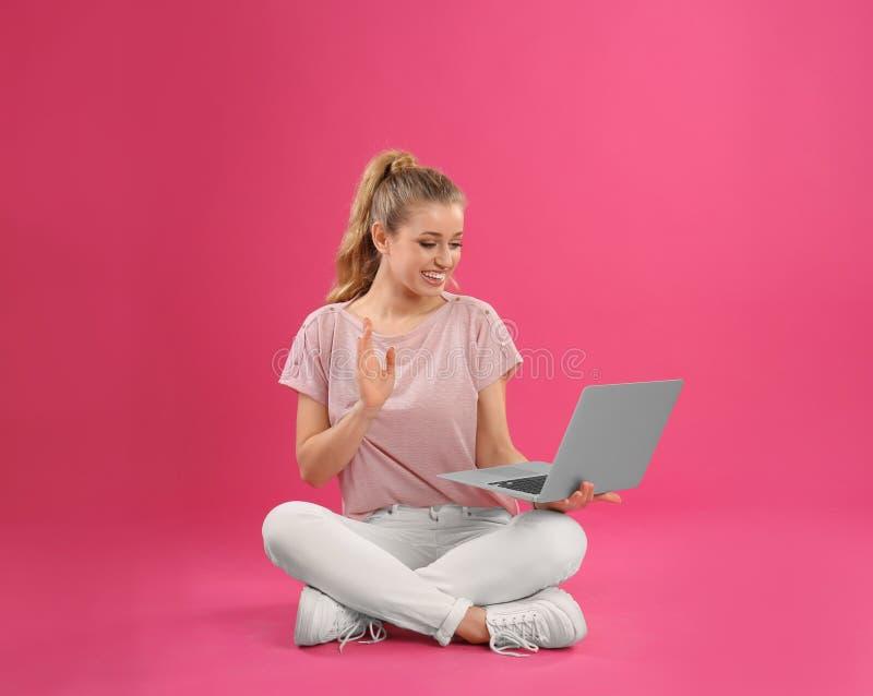 Härlig ung kvinna som använder bärbara datorn på rosa färger royaltyfria bilder