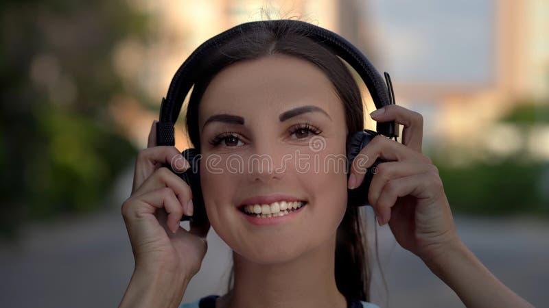 Härlig ung kvinna som använder den smarta telefonen och att skriva meddelanden och att lyssna till musik som dricker kaffe, medan arkivbilder