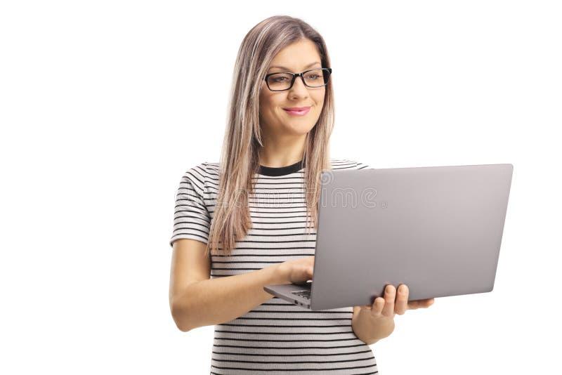 Härlig ung kvinna som använder en bärbar datordator royaltyfri bild