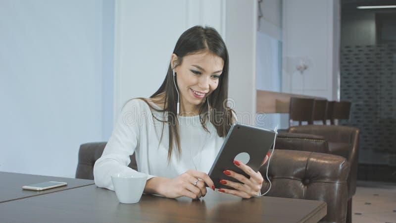 Härlig ung kvinna som använder en minnestavlaPC för att göra en video appell, medan sitta i ett kafé royaltyfri fotografi