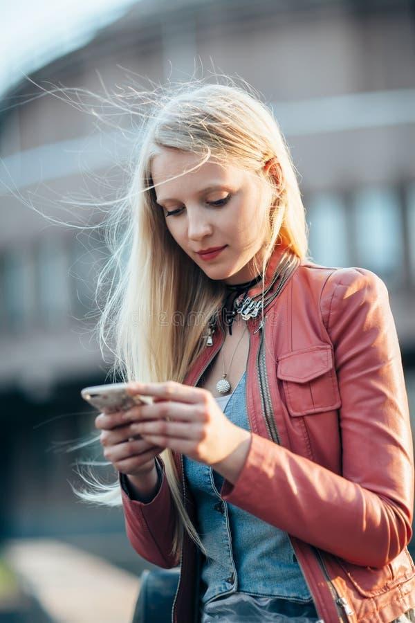 Härlig ung kvinna som använder hennes mobiltelefon i gatan royaltyfri fotografi