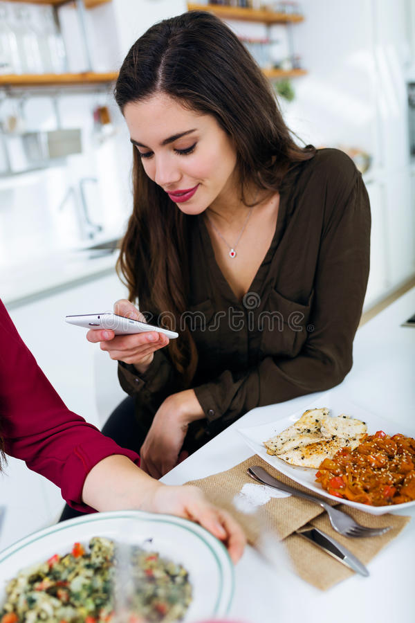 Härlig ung kvinna som använder hennes mobiltelefon, medan äta royaltyfria bilder