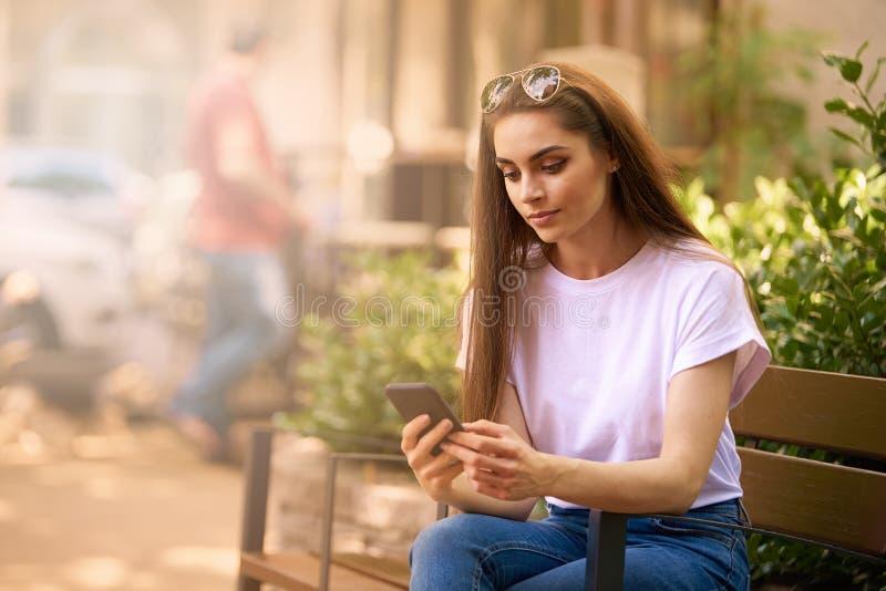 Härlig ung kvinna som använder hennes mobiltelefon- och textmessaging, medan sitta på bänk på gatan arkivfoto