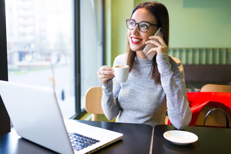 Härlig ung kvinna som använder mobiltelefonen, medan dricka kaffe i kafét arkivfoto