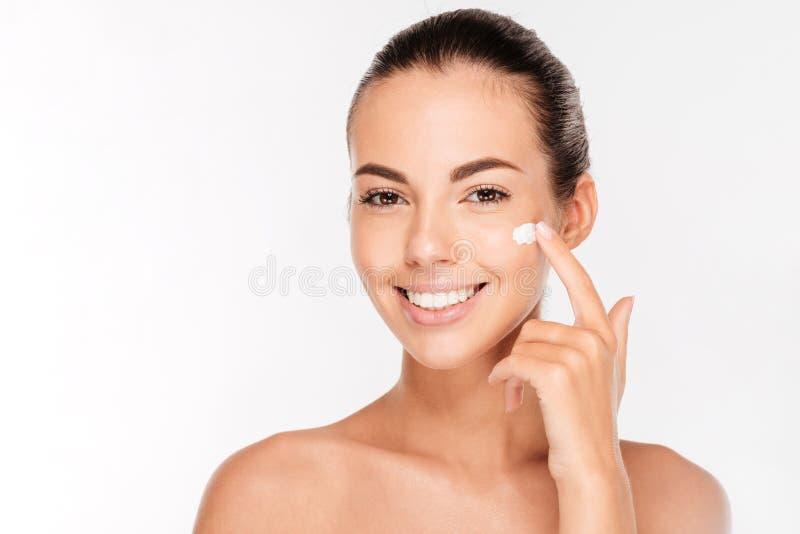 Härlig ung kvinna som applicerar kräm- behandling för skönhetsmedel på hennes framsida arkivfoto