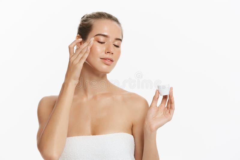 Härlig ung kvinna som applicerar kräm- behandling för skönhetsmedel på hennes framsida som isoleras på vit bakgrund royaltyfria foton