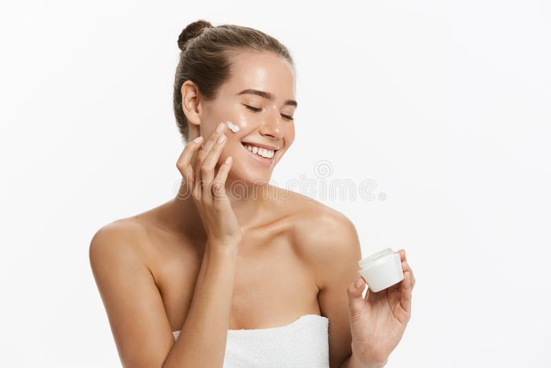 Härlig ung kvinna som applicerar kräm- behandling för skönhetsmedel på hennes framsida som isoleras på vit bakgrund fotografering för bildbyråer