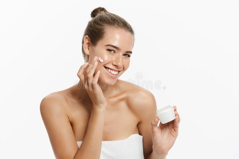 Härlig ung kvinna som applicerar kräm- behandling för skönhetsmedel på hennes framsida som isoleras på vit bakgrund arkivfoto