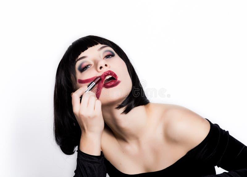 Härlig ung kvinna som applicerar mörker - röd läppstift, fula färgade kanter På en vit bakgrund royaltyfria foton