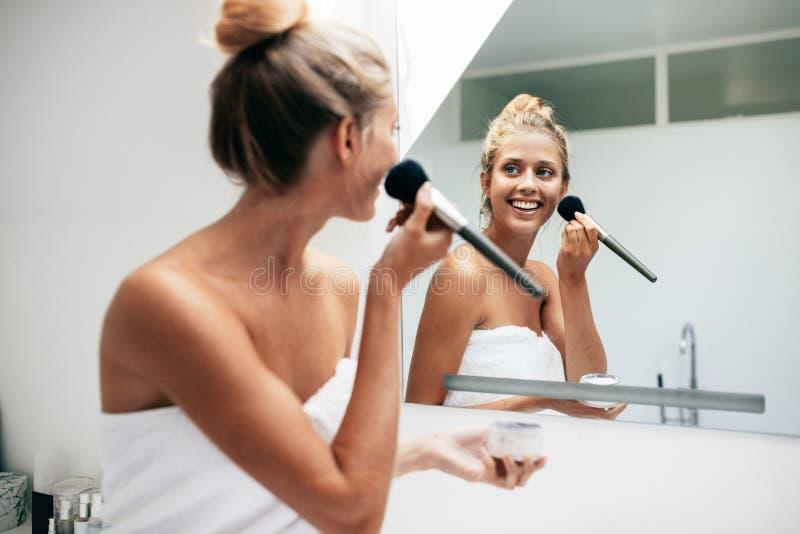 Härlig ung kvinna som applicerar makeup i badrum arkivfoton