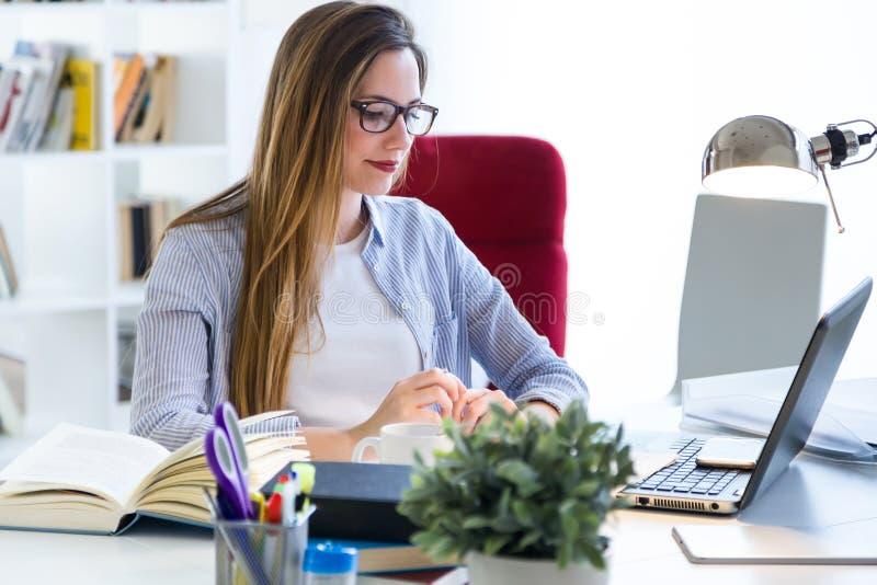 Härlig ung kvinna som arbetar med bärbara datorn i hennes kontor arkivfoto