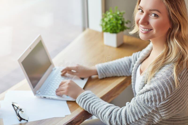 Härlig ung kvinna som arbetar med datoren på kafémaskinskrivning på ett tangentbord och ser kameran Top beskådar arkivfoton