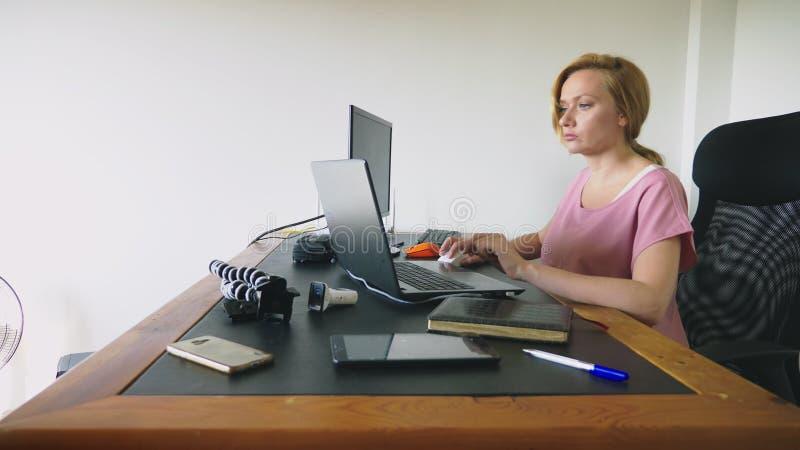 Härlig ung kvinna som arbetar på en bärbar dator och en dator, medan sitta på ett skrivbord arkivbild