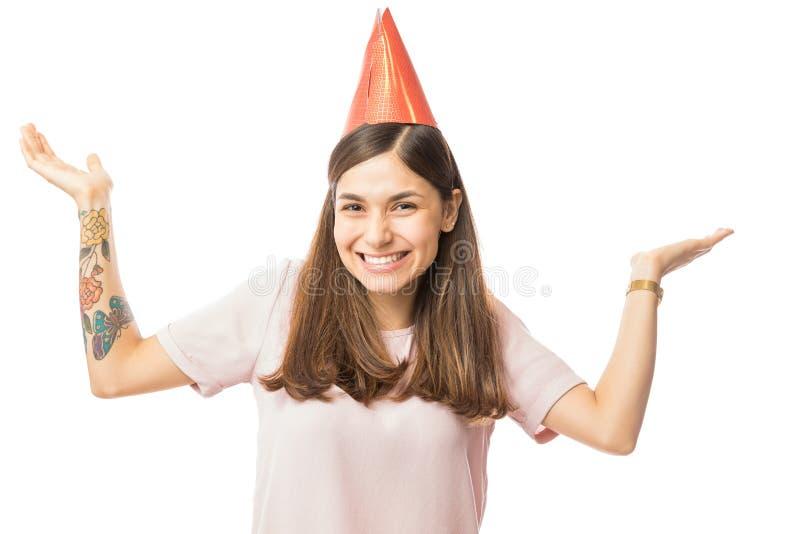 Härlig ung kvinna som bär den pappers- hatten, medan lyfta henne armar royaltyfri bild