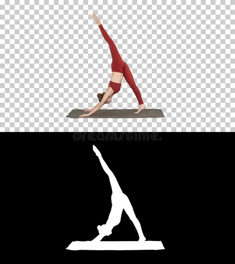 Härlig ung kvinna som bär den röda sportswearen som gör yoga- eller pilatesövningen som står i variation av Natarajasana, alfabet arkivfoto