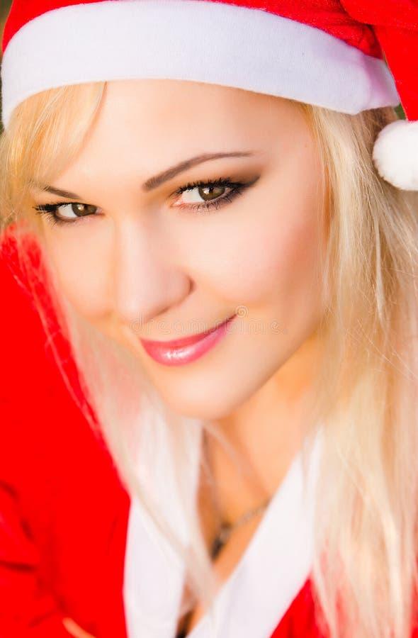 Härlig ung kvinna som bär den Santa Claus dräkten royaltyfri bild