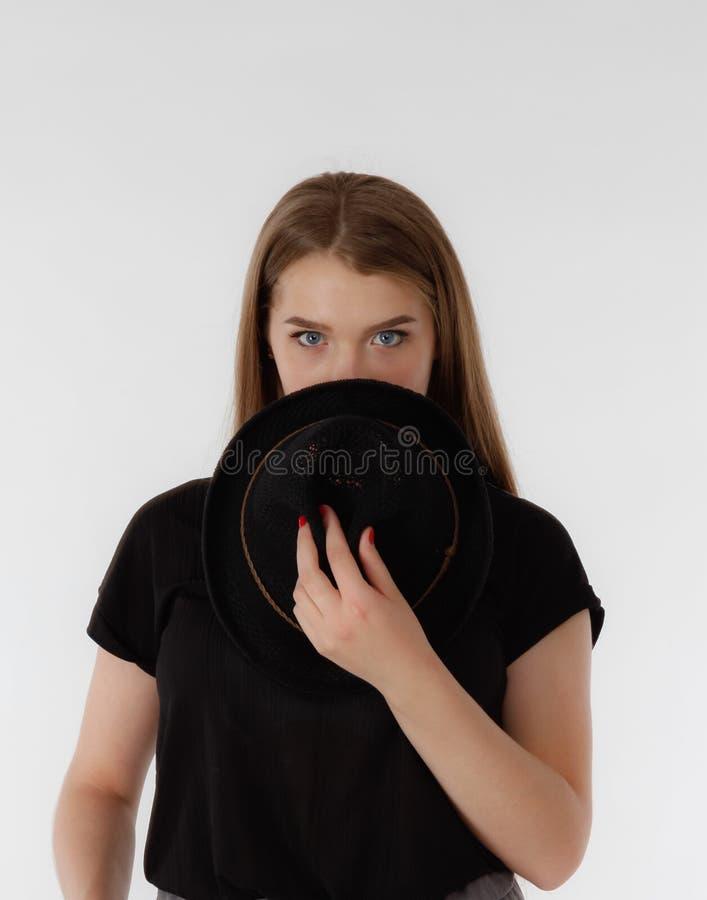 Härlig ung kvinna som bär den svarta hatten på ljus bakgrund Ingen framsida royaltyfri fotografi
