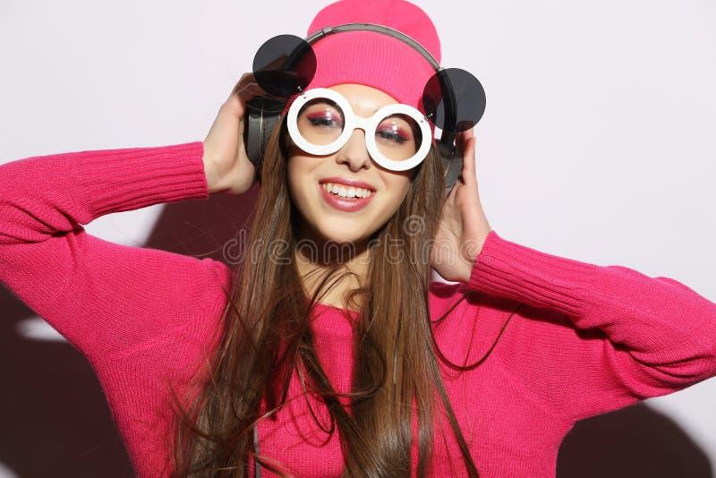 Härlig ung kvinna som bär rosa kläder som lyssnar till musik i hörlurar på vit bakgrund royaltyfria foton