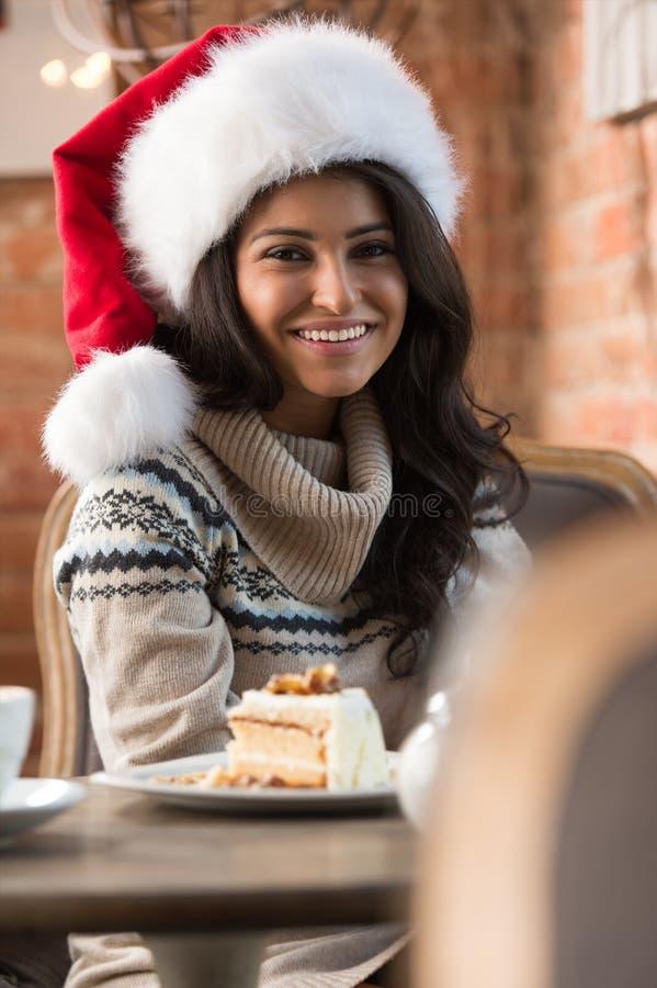 Härlig ung kvinna som bär Santa Claus rött hattsammanträde på caf arkivfoton