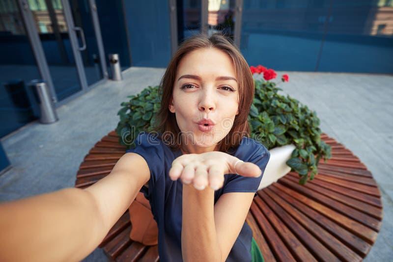 Härlig ung kvinna som blåser en kyss, medan posera för en selfie royaltyfria bilder